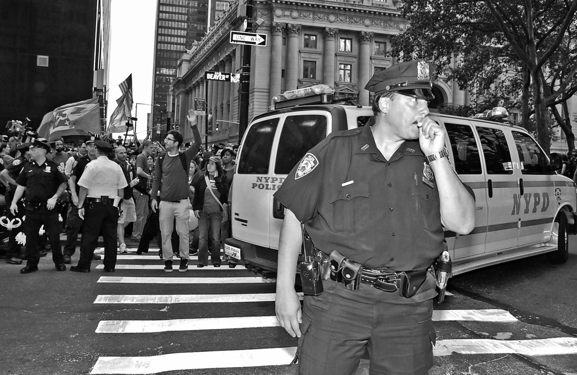 Occupy Wall Street NYPD Old School officer with protesters in backgroun