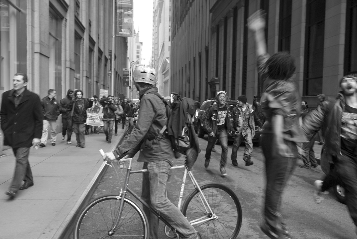Occupy Wall Street protesters running past biker